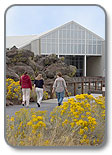 3 people walking into a wildflower lined path to the Oregon Trail Interpretive Center
