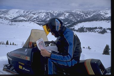snowmobiler looking at map