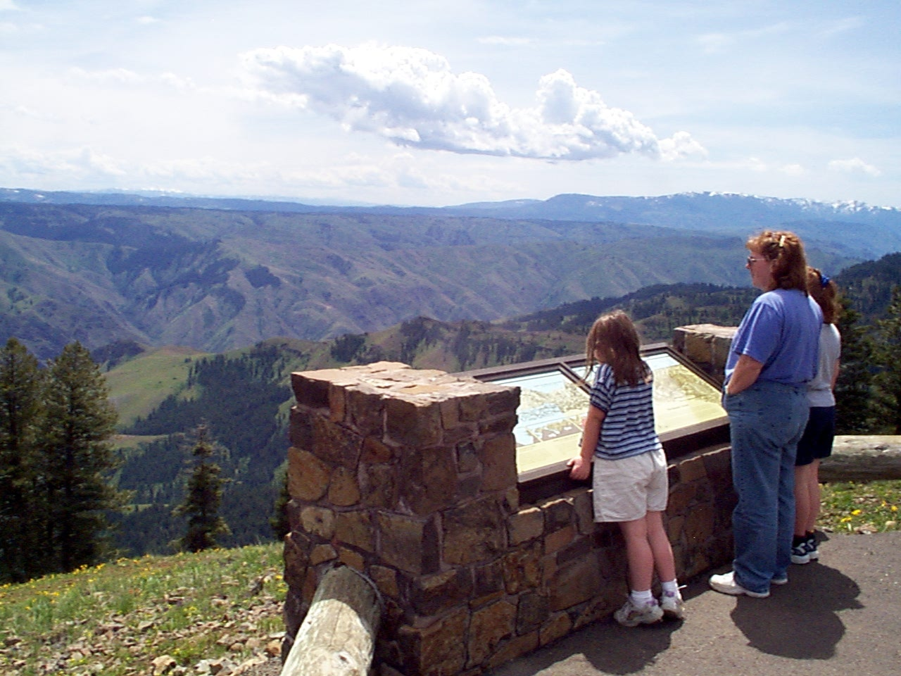A woman and children reading an interpretive panel at Hells Canyon Overlook