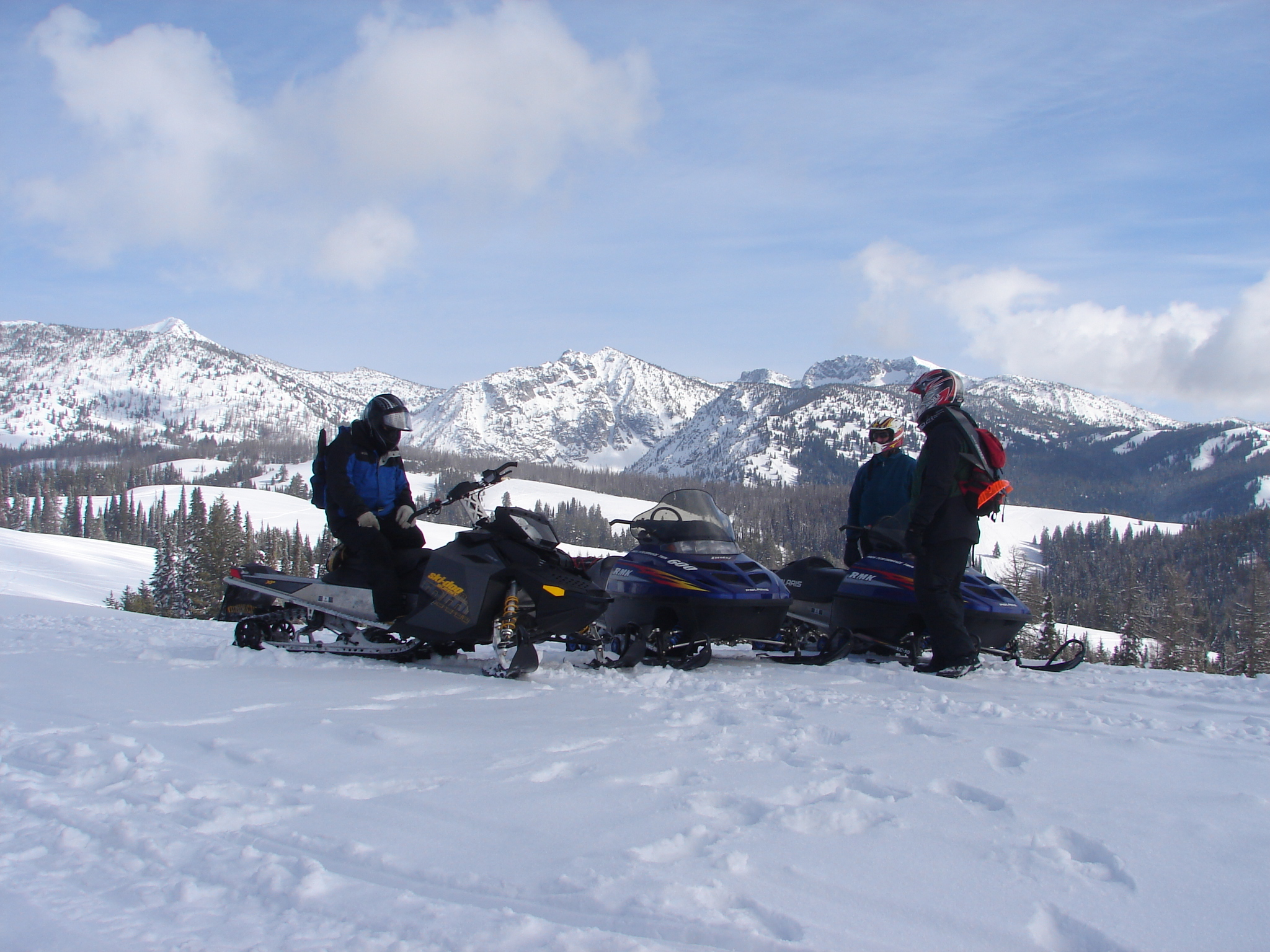 3 snowmobile riders visting with snowy mountains in background