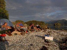Campers soak up late afternoon soon on a gravel beach of a forested island.