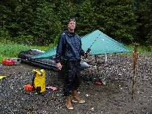 A rain-soaked boater stands with a radio on shore next to a tarp and zodiac raft.