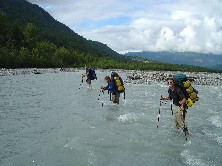 Three backpackers lean on their trekking poles as they ford a gray glacial river.