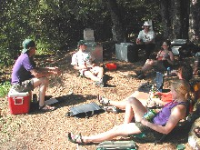 A group of campers talks in a circle in their forested camp.