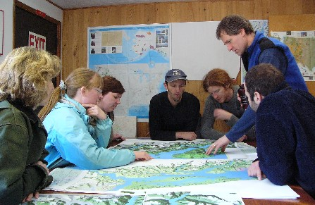 A group of women and men discuss their expedition over maps spread out on a table.