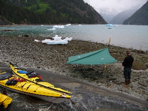 A kayaker erects a tarp in the high intertidal zone.