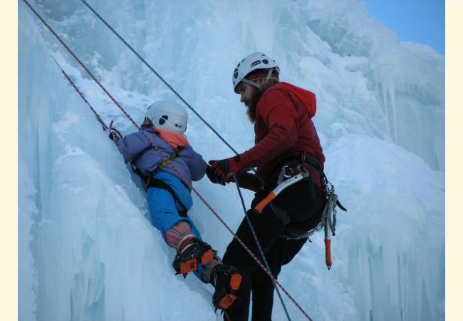 image ofice climber helping child with ropes on ice wall