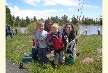 Photo of a family with the kids holding up the fish they caught for the day at Moose Pond.