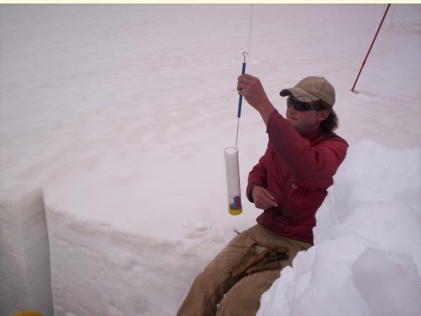 image of youngman measuring snow in cylinder