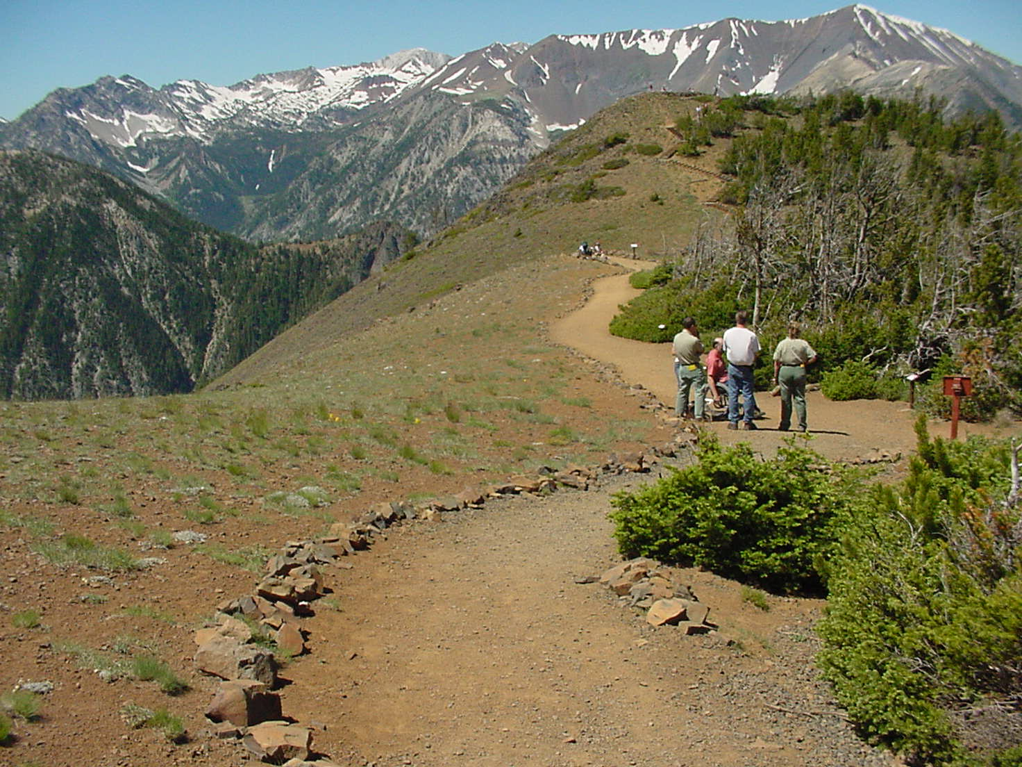 People walking down a sandy trail with mountains in background