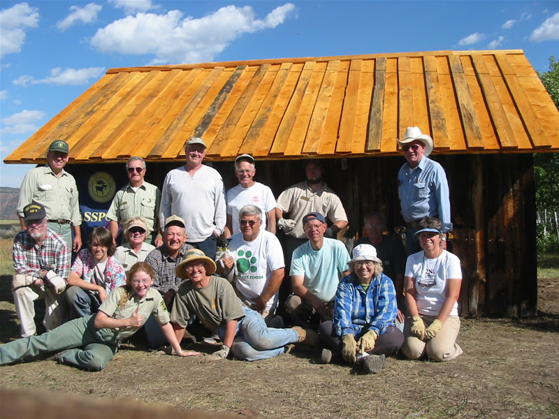 2004 PIT volunteers in front of the first blacksmith shop with newly replaced roof.