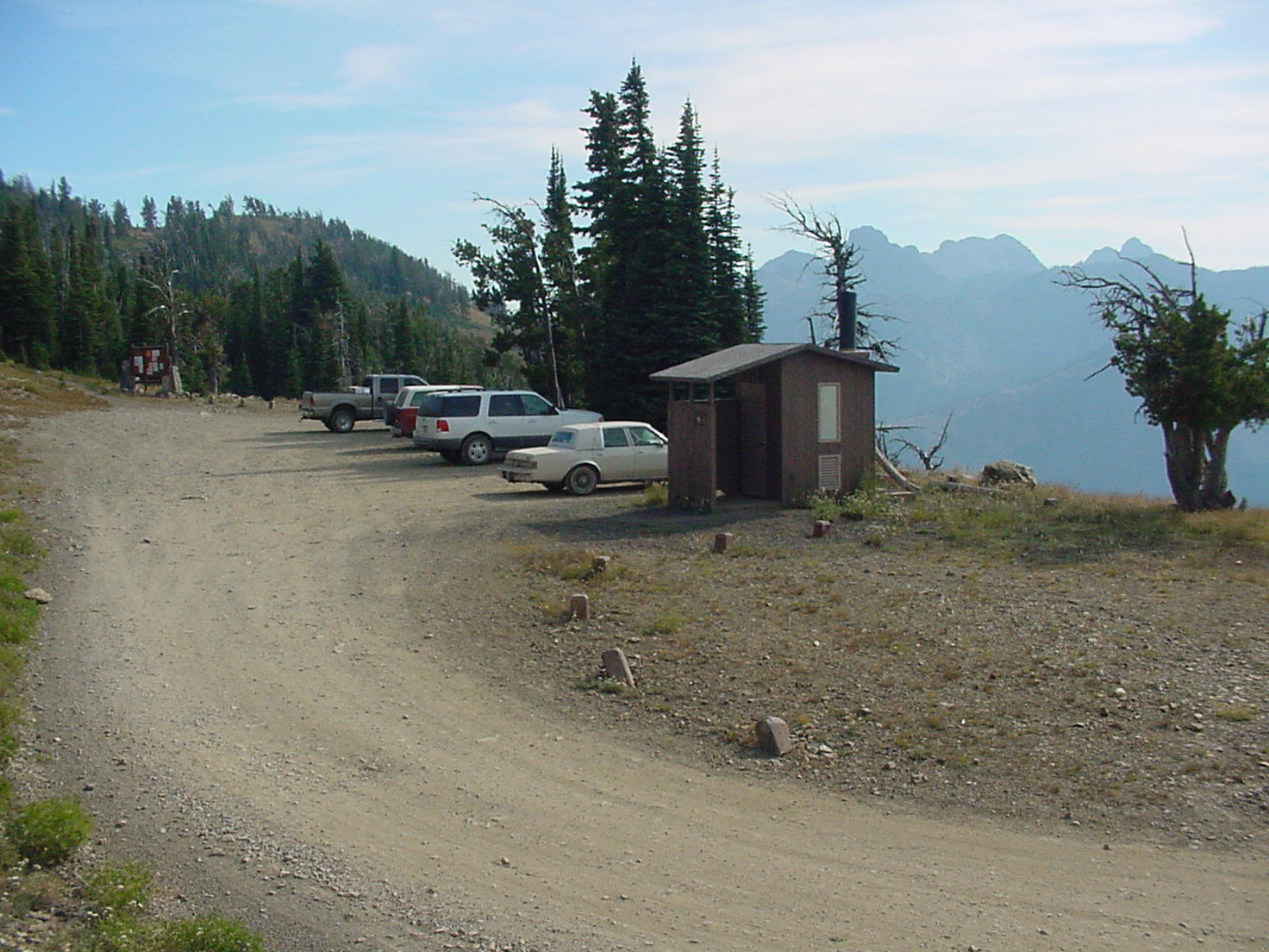 Cars and trucks parked at a mountain trailhead