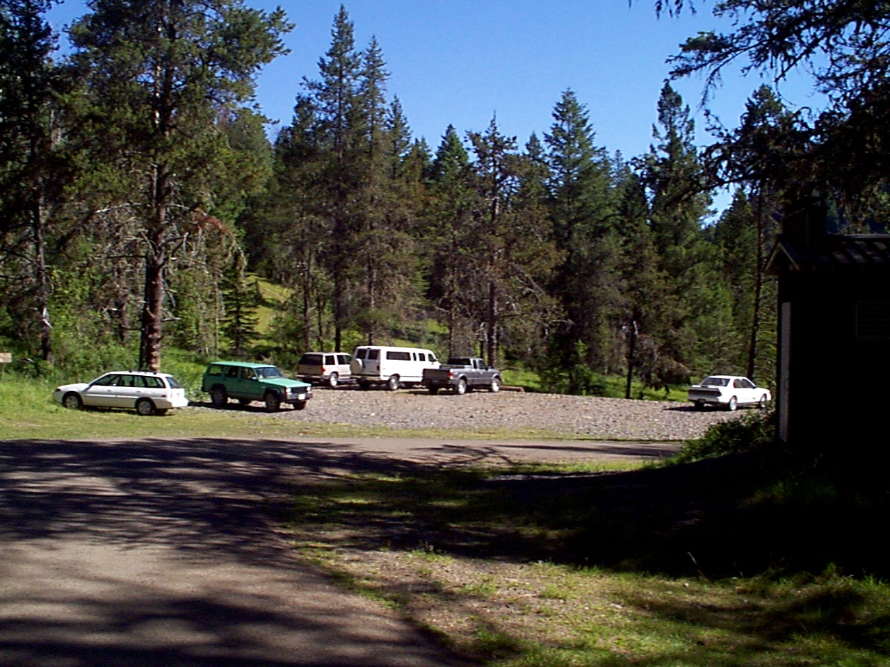 Large hiker trailhead with trucks and pine trees in background