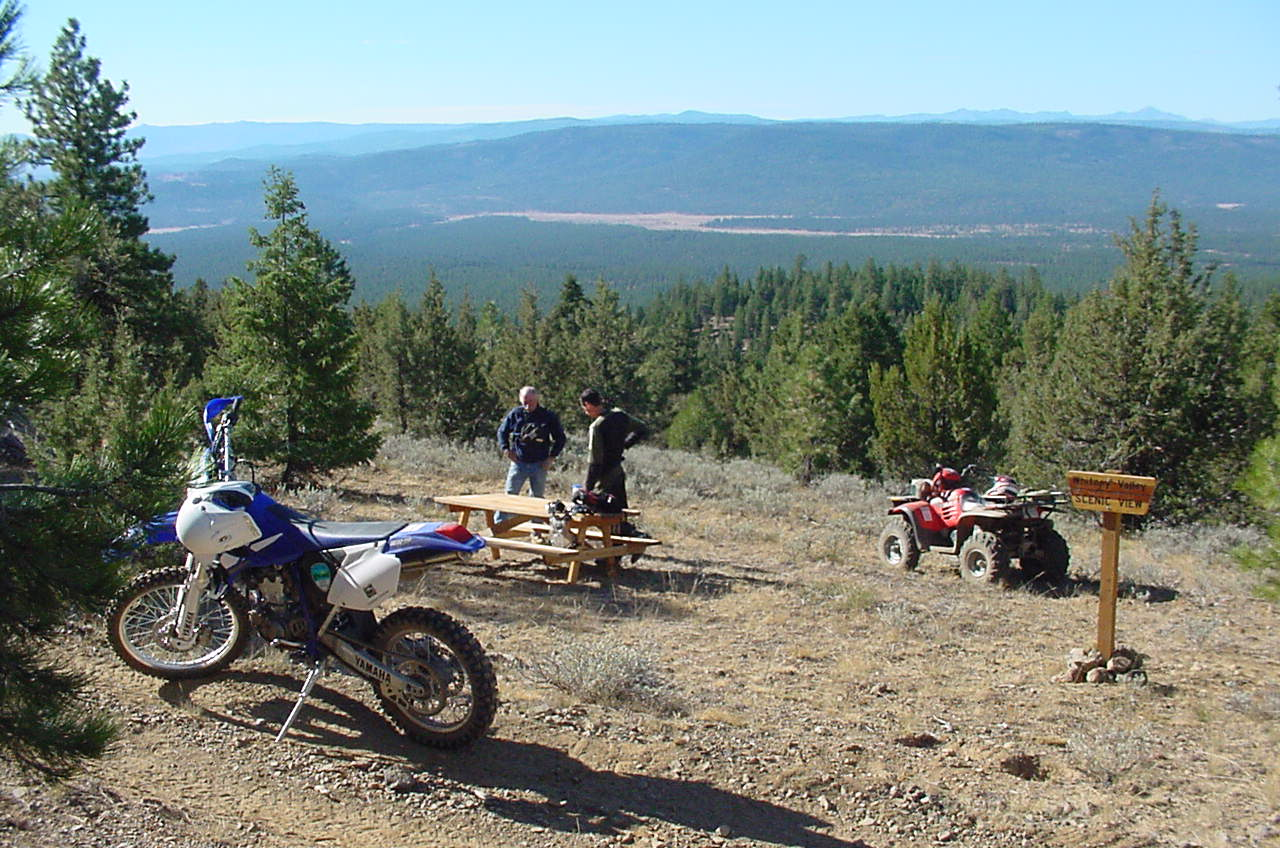 ATV and motorcycle riders taking break overlooking a forest view