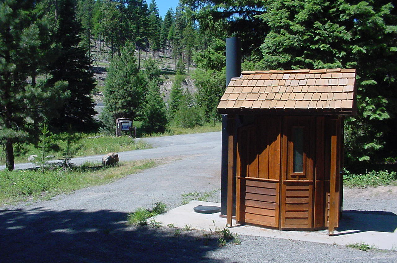 Oregon campground toilet and camping area in pine forest