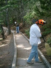 Two volunteers sweeping the nature trail at Cienega Picnic Area