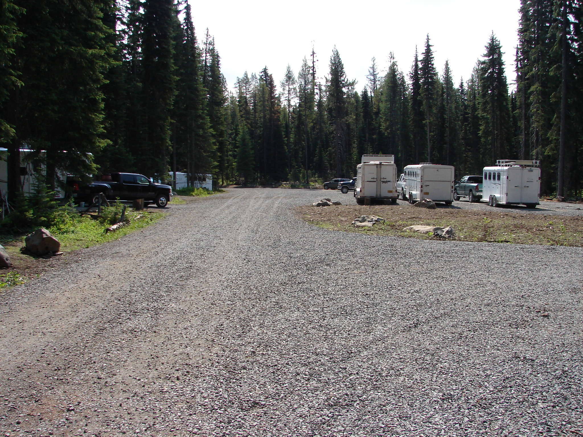 Large gravel trailhead parking area with trucks and horse trailers