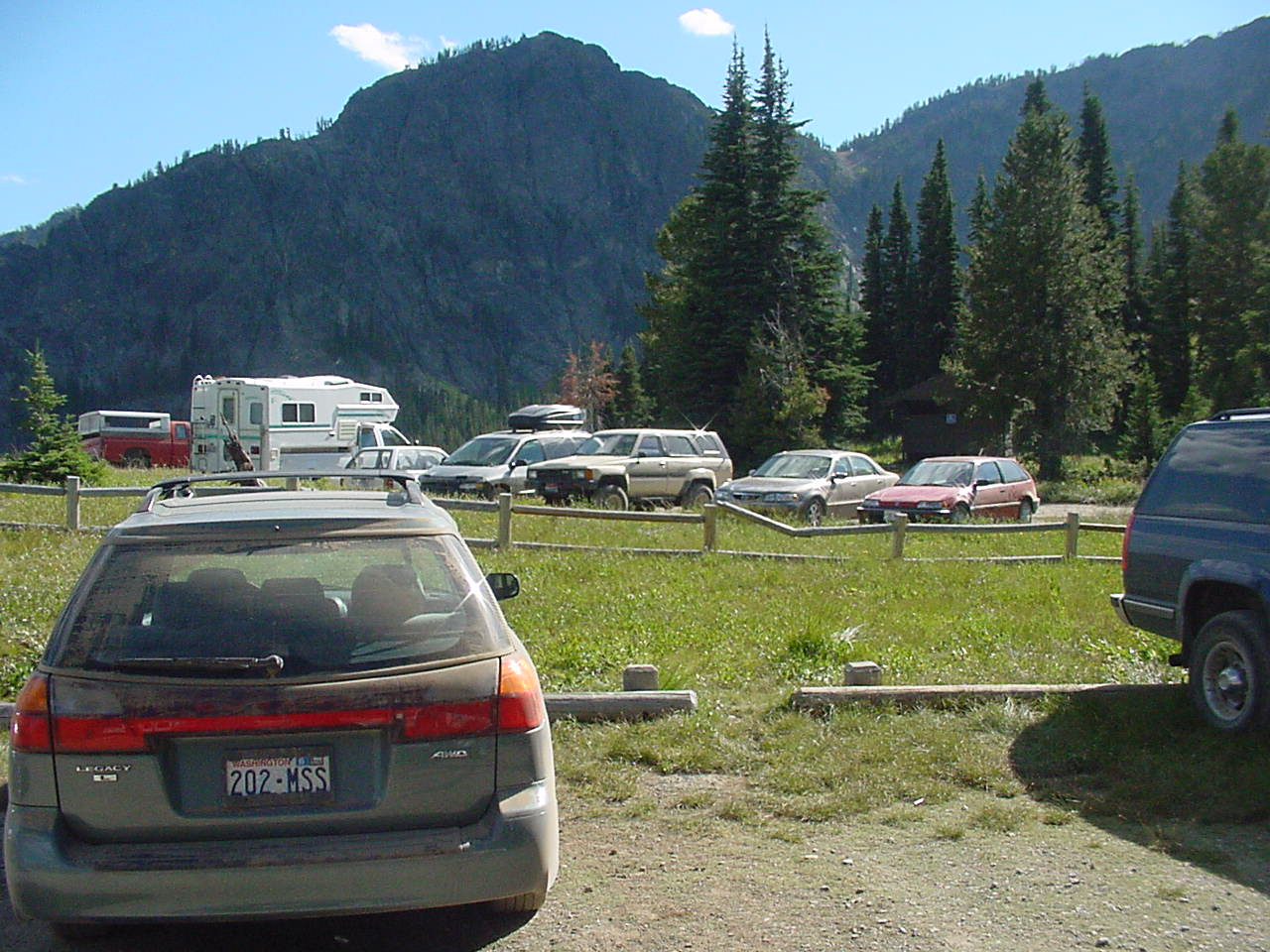 Cars parked at a forest trailhead with mountains in background