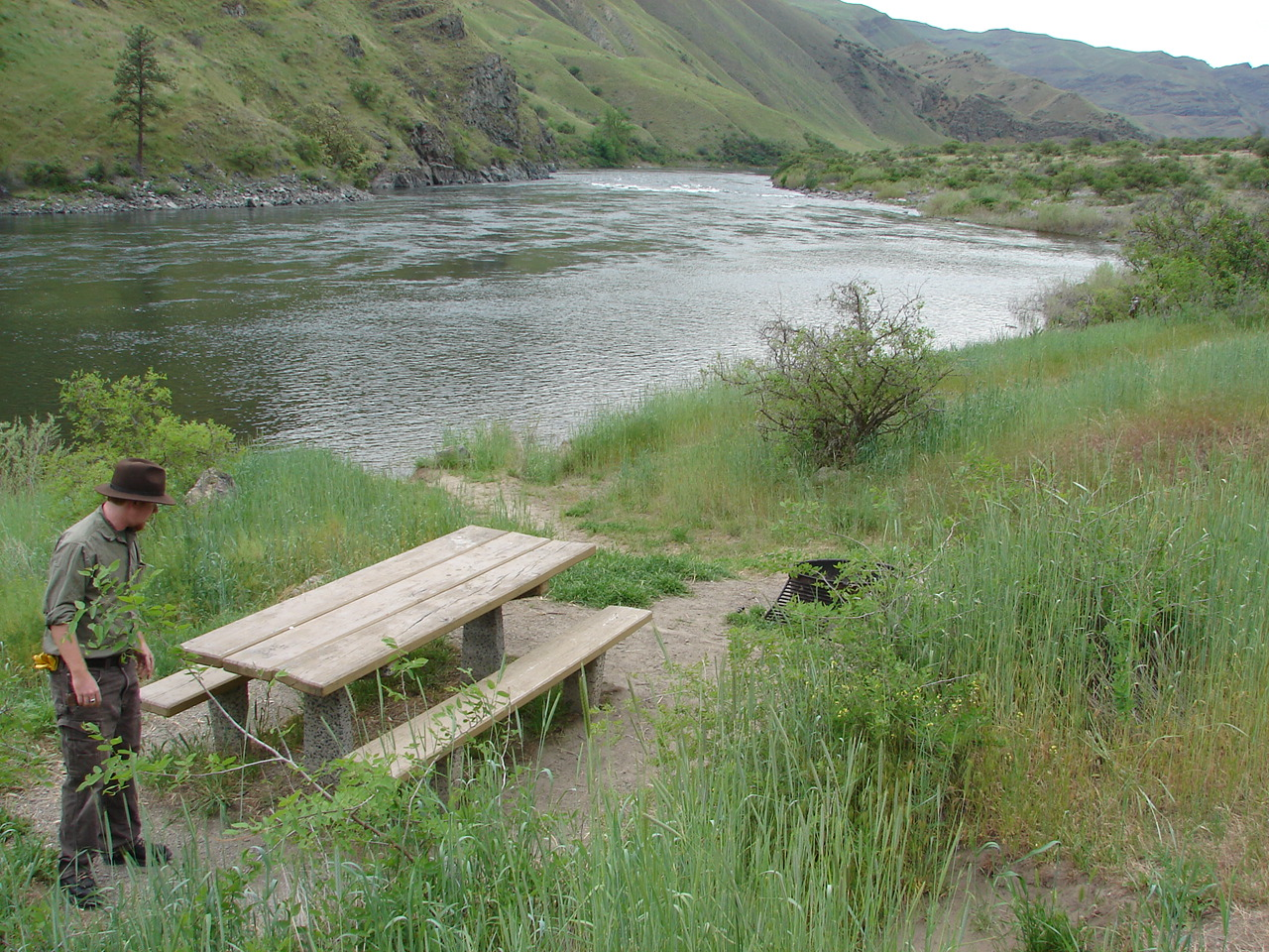 Man standing near picnic table by Snake River