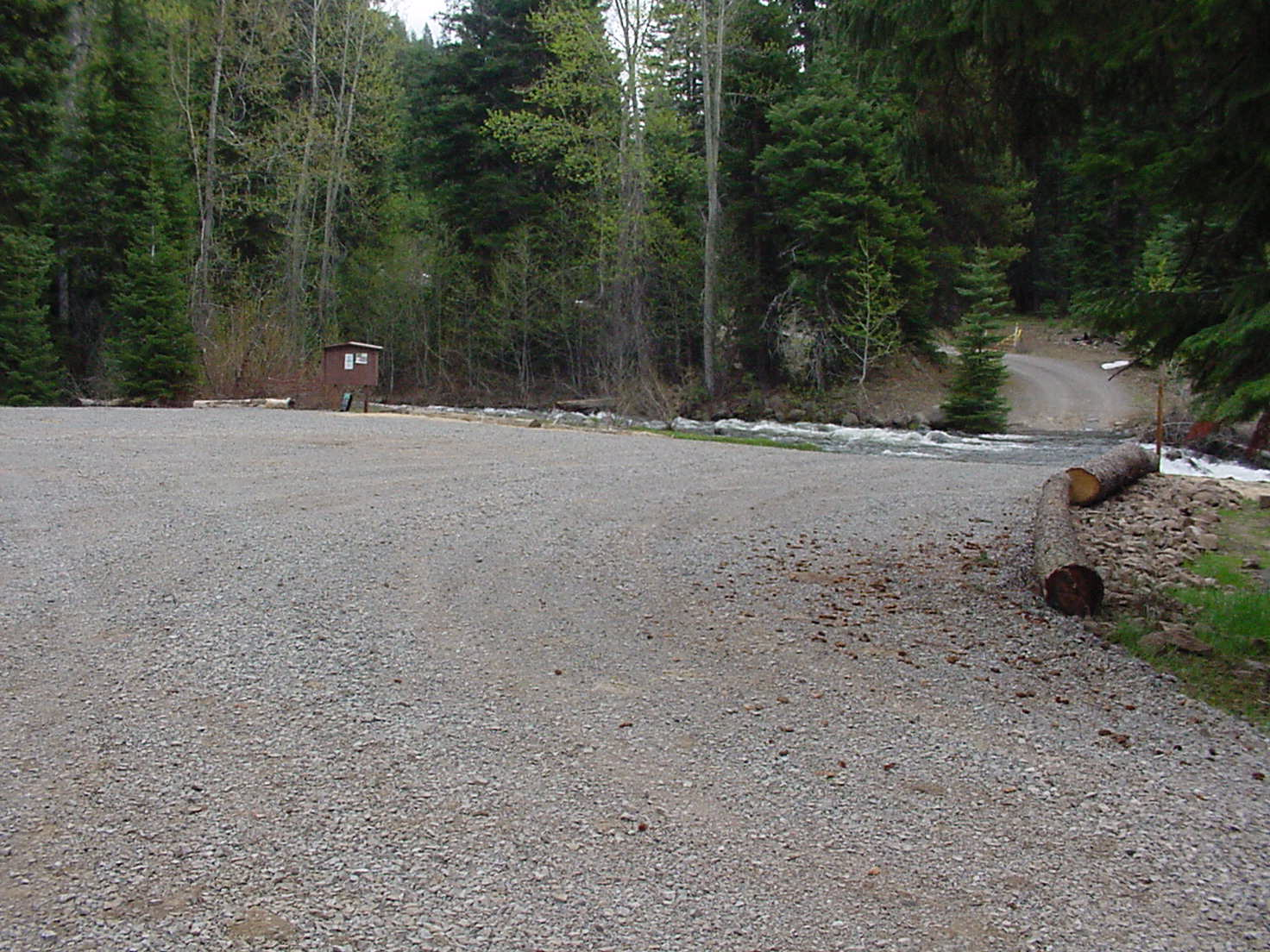 Large gravel trailhead parking area with pine trees