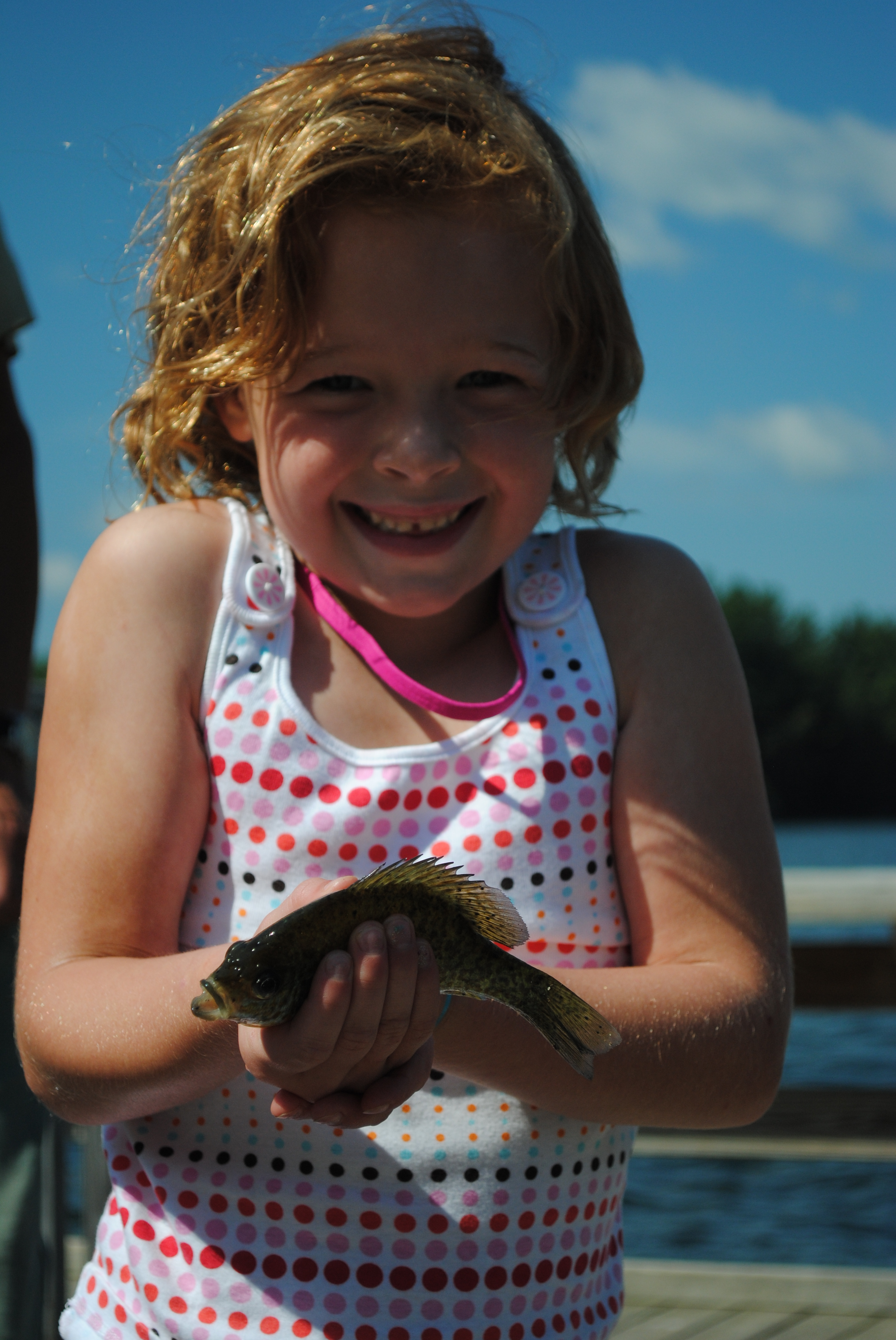 Girl smiling, holding up small fish she has just caught.
