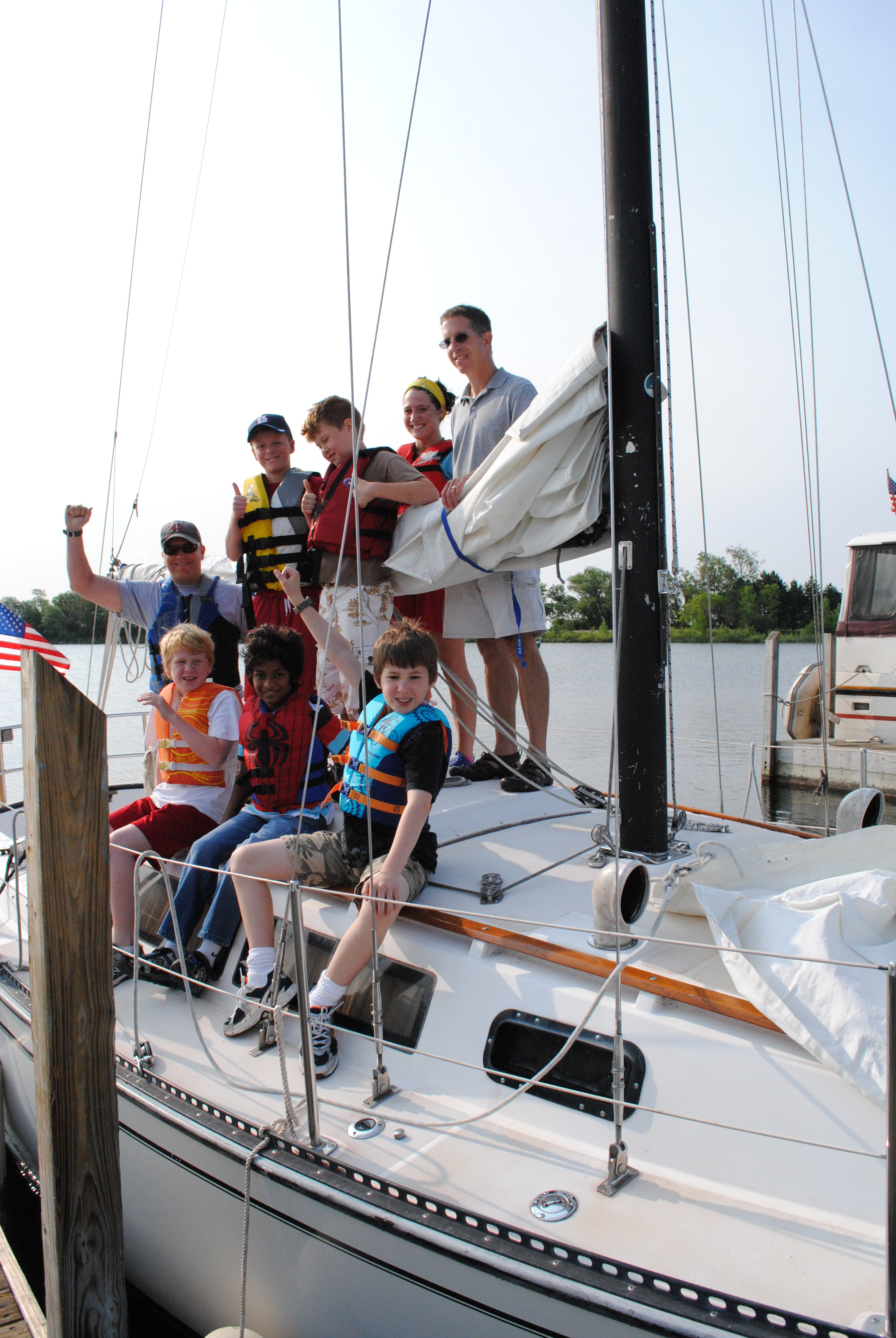 Kids, Forest ranger and Y staff smile and wave from sailboat.