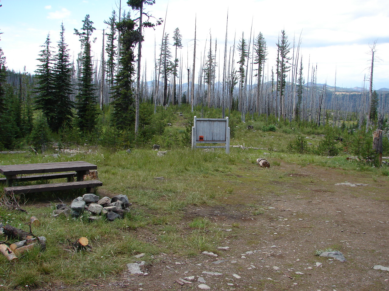 Mountain trailhead parking area with a sign and picnic table