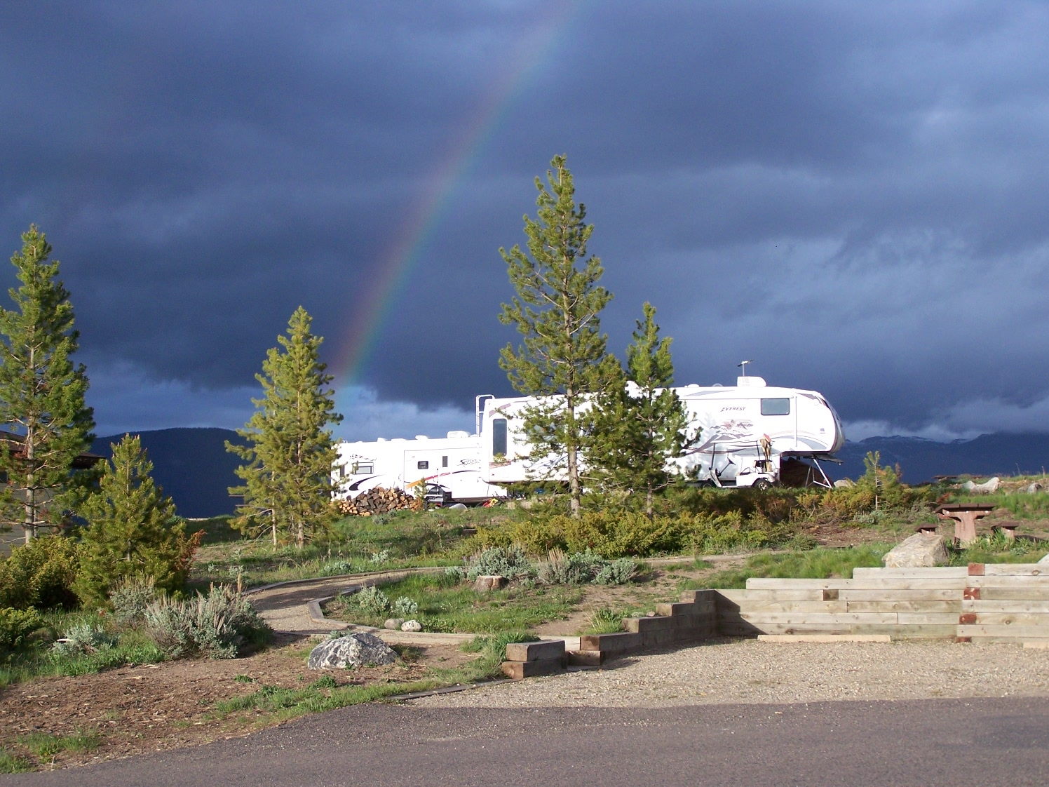 Rainbow over white trailer in Stillwater campsite.