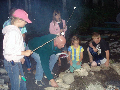 Father and children roasting marshmallows
