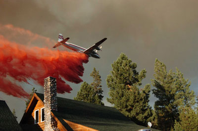 Air tanker dumps fire retardant near a home