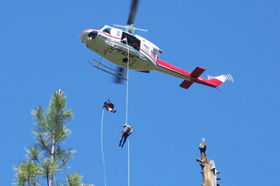 Fire fighters rappel out of helicopter