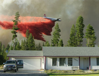 Air tanker dumps fire retardant to protect a house