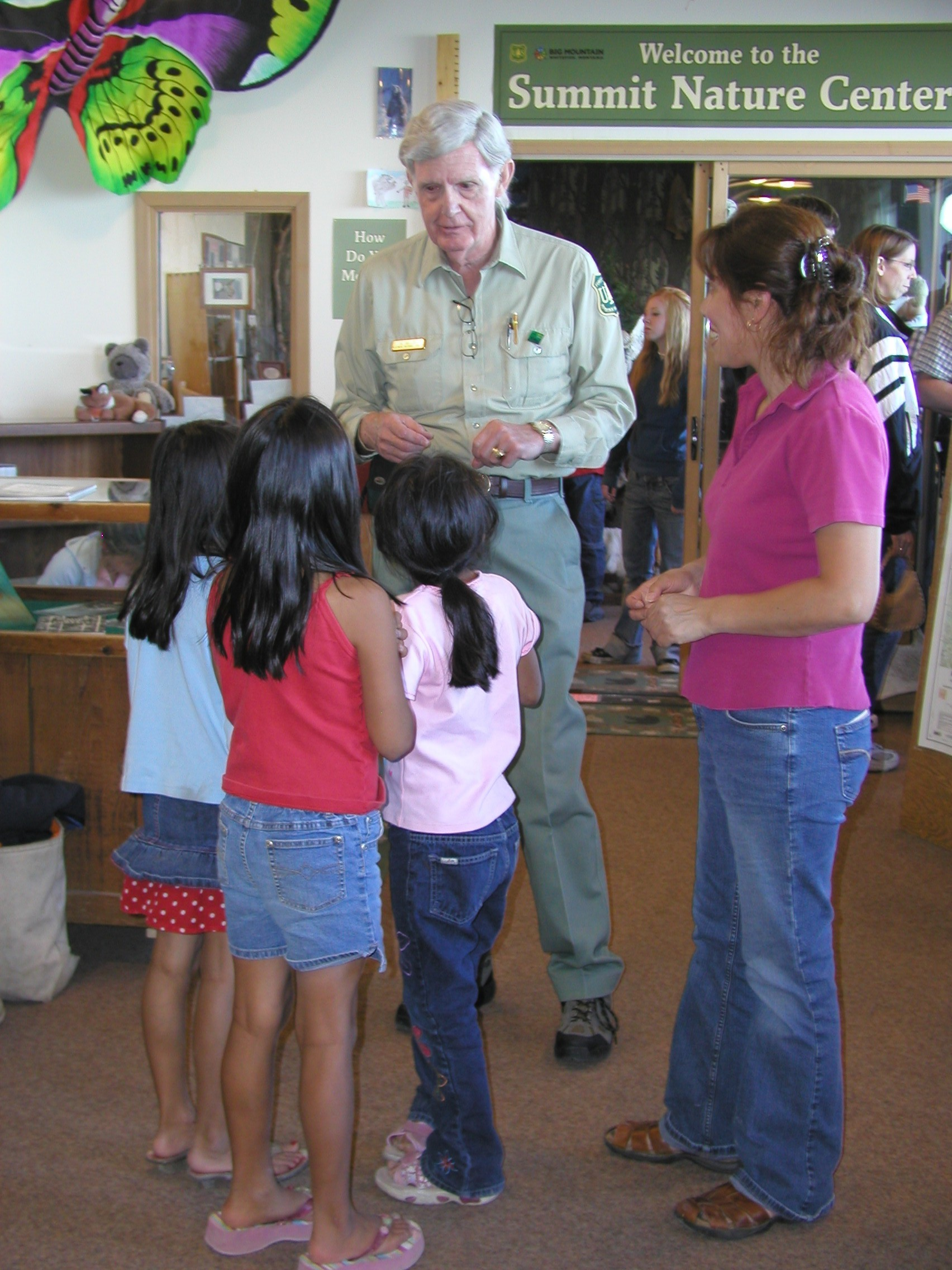 Ranger greets family inside the nature center