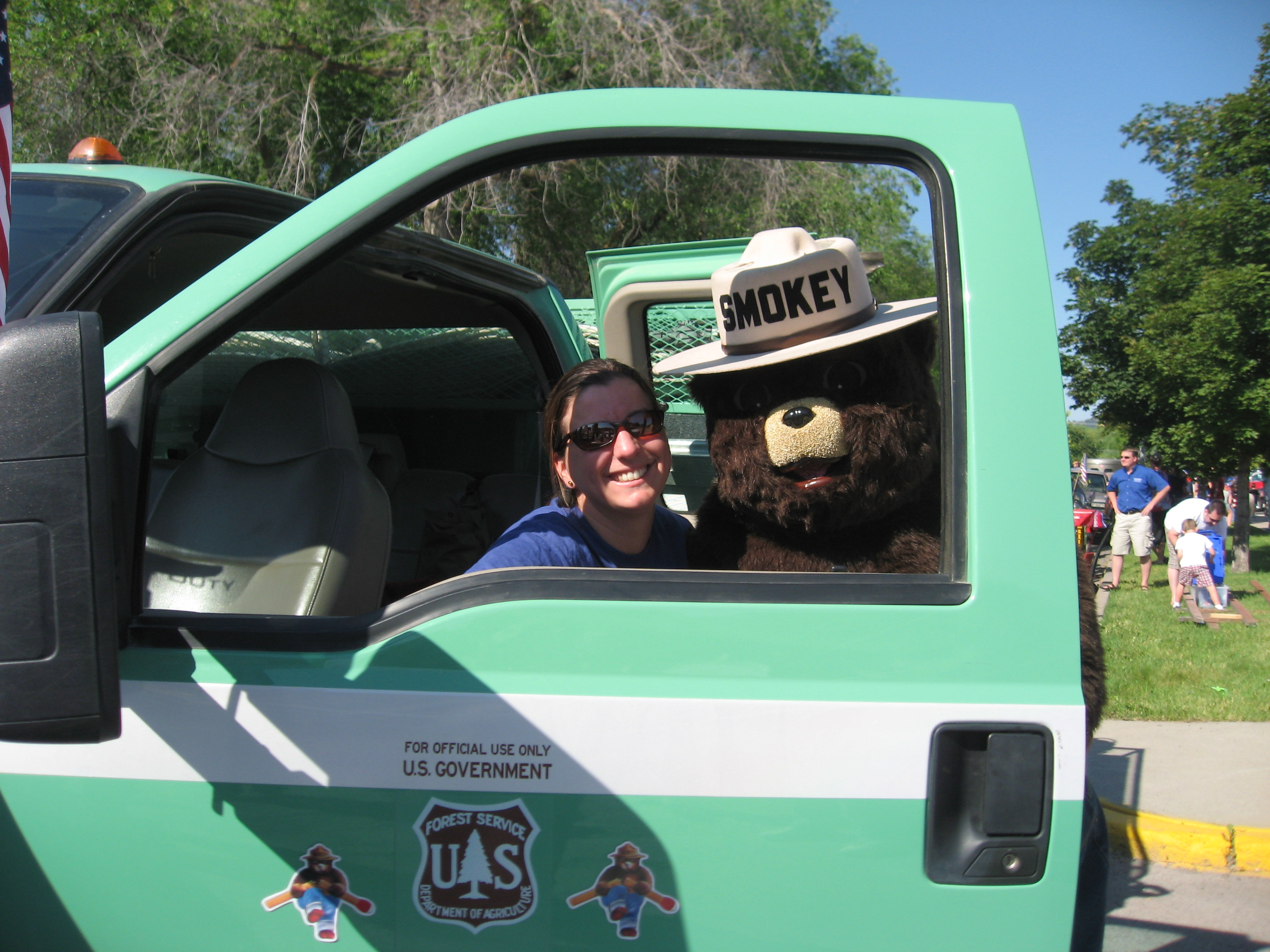 Smokey Bear poses with firefighter looking thru truck window