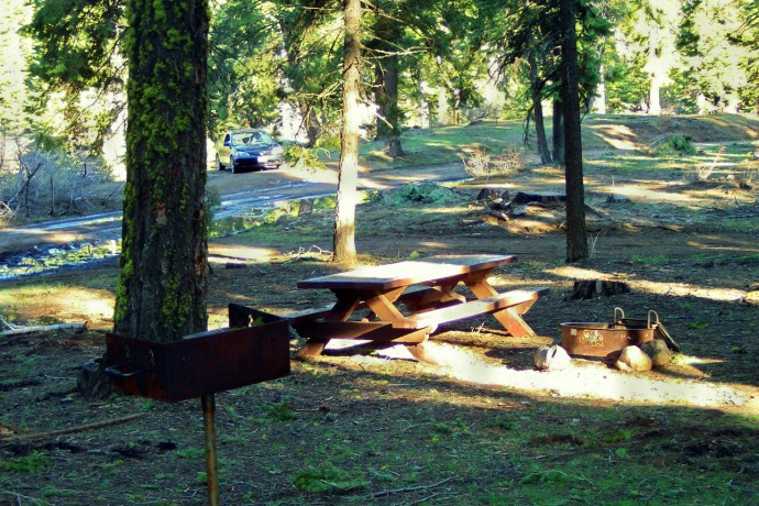 A table, fire ring and barbecue near the water at Stough Campground.