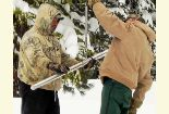 Two men weigh a tube full of snow to determine water content.