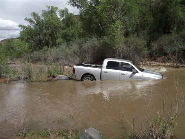partially submerged truck crossing creek