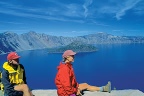 two hikers looking at Crater Lake, OR