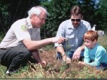 photo of a forester advising a family about a tree seedling