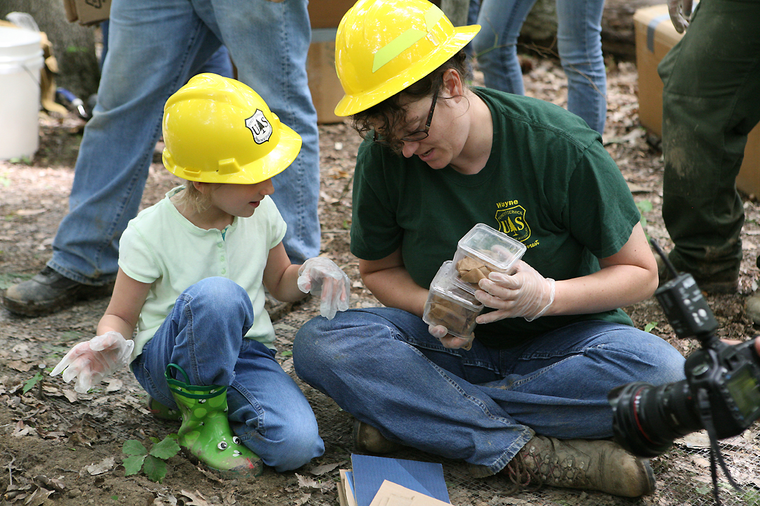 Cheryl Coon, Botanist, hands a pair of American burying beetles to a child.