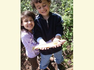 A brother and sister show off their big smiles and rainbow trout caught at Clear Lake.