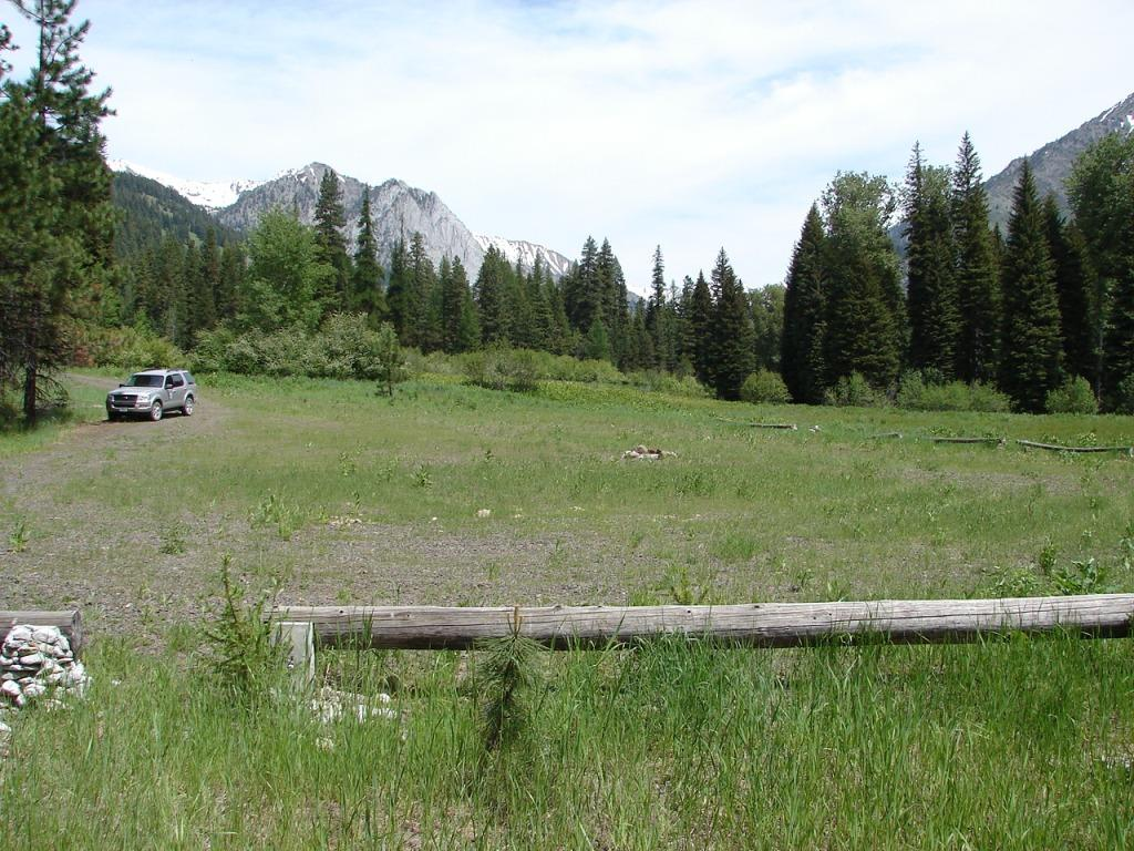 Small gravel trailhead with mountains in background