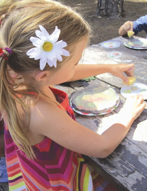Little girl making art project outdoors