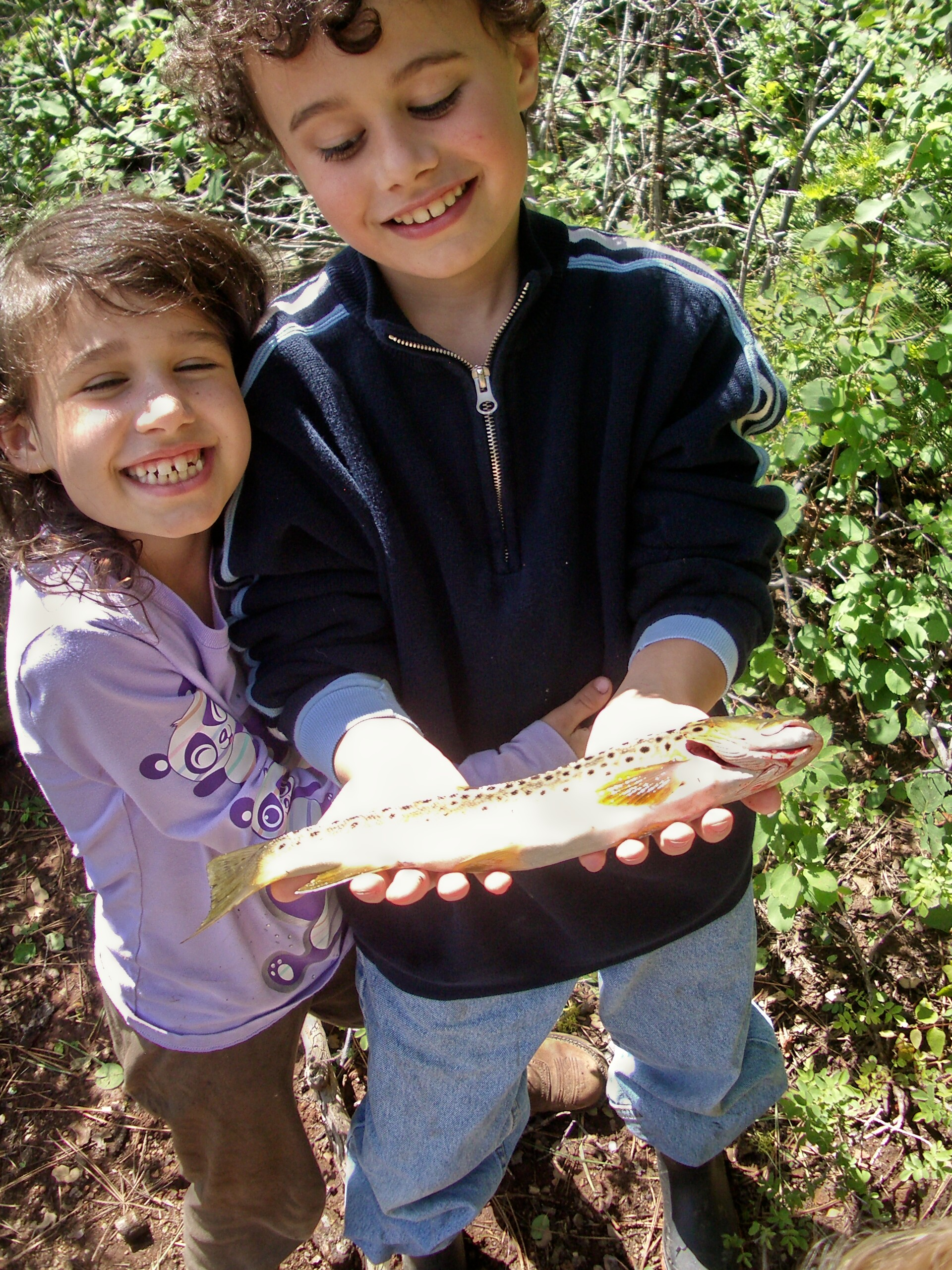 A boy and his sister with big smiles hold out a fish they caught.
