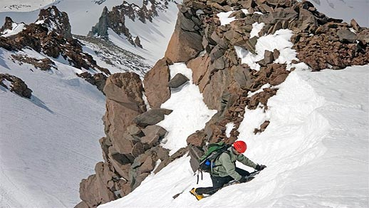 Backpacker in hard hat climbs a snowy, rocky mountain.