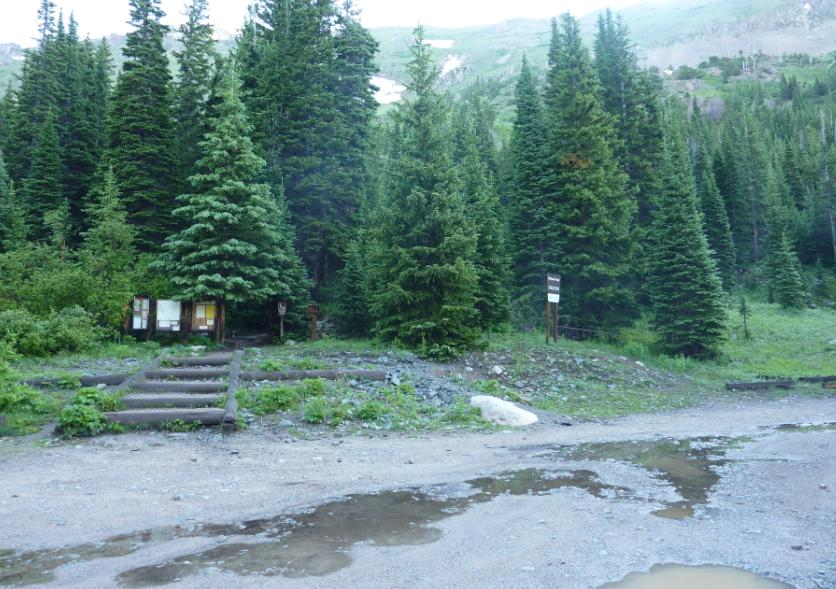 Photo of the small parking area for the 4th of July Trailhead at the end of a rocky road