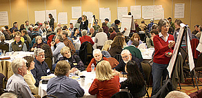 Photo of public collaborative meeting with people sitting at tables and talking.