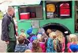 15 children crowd around a fire fighter while he shows them the equipment on his engine.