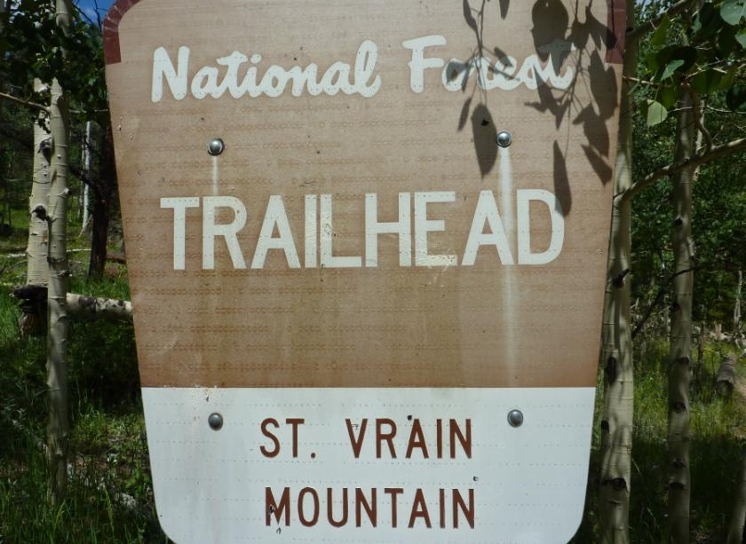 Photo of the St Vrain Mountain Trailhead sign located in the small parking area