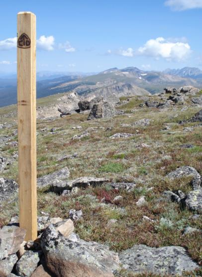 Photo of the Continental Divide Trail marker on top of Rogers Pass